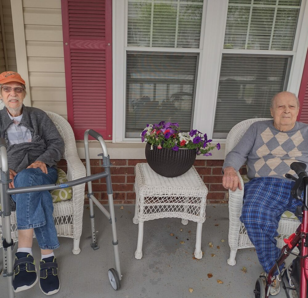 Two senior men at a front porch social at a senior living community in Jeffersonville, Indiana.