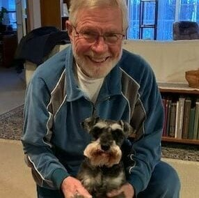 Senior man smiles with his small dog at a senior living community in Fitchburg, Wisconsin.