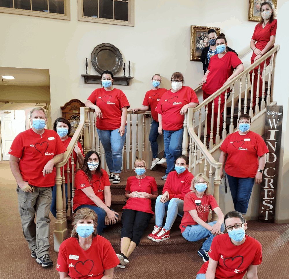 Employees-pose-in-face-masks-and-red-shirts-on-staircase-in-senior-living-facility.