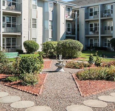 A well-landscaped courtyard with a paved walking path and fountain feature.