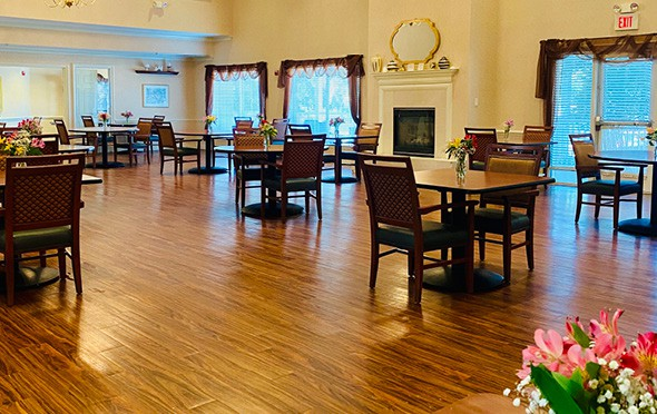 A spacious dining area with flower centerpieces on all tables and a fireplace in North Richland Hills, Texas.