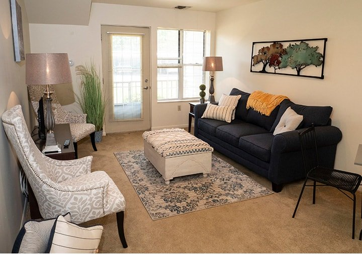 A bright, beautiful living room in a model apartment with plenty of comfortable seating and a door leading out to a patio.