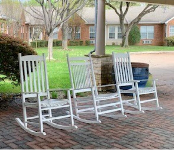 Senior living community rocking chairs in outdoor courtyard in Arlington, Texas.
