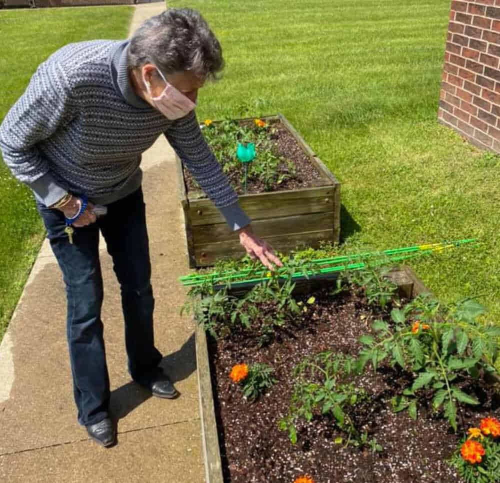 A resident checking on some marigolds in Canton Regency's courtyard raised garden beds.