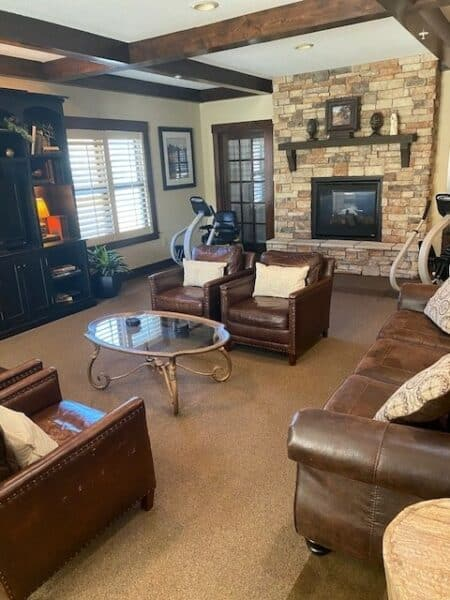 Club room with stationery bike, comfortable couches and fireplace at senior living facility in St. Joseph, Missouri.