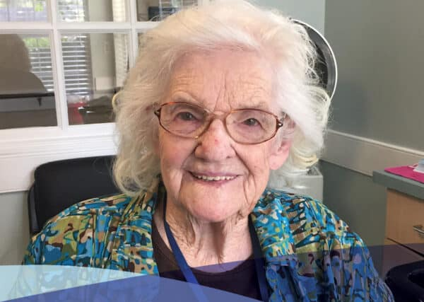A capital senior living community resident smiling as she enjoys a sunny day relaxing in the community salon.