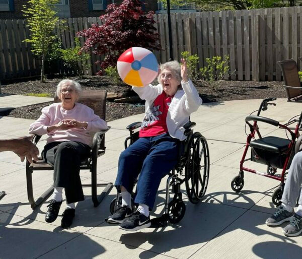 Seniors in a memory care program sitting outside on patio playing a game.