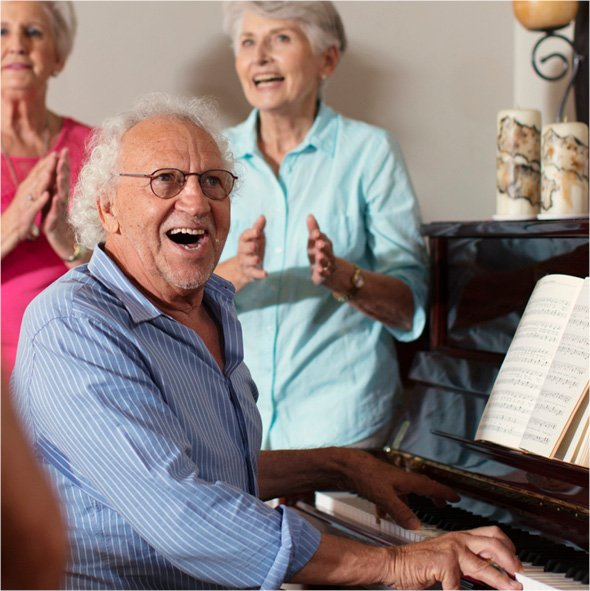 A senior smiling and playing piano while fellow residents sing and clap along in their senior living retirement community.
