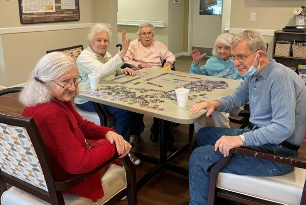 group of seniors solve a puzzle together at a table