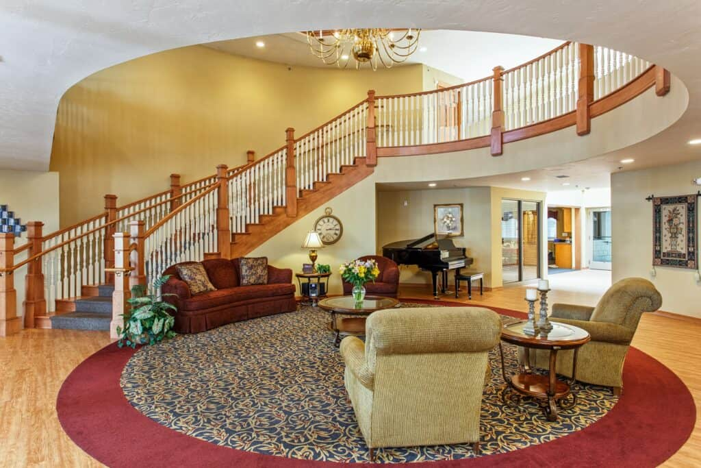 Lobby with a grand staircase, high ceilings and ample seating at senior living community in Green Bay, Wisconsin.