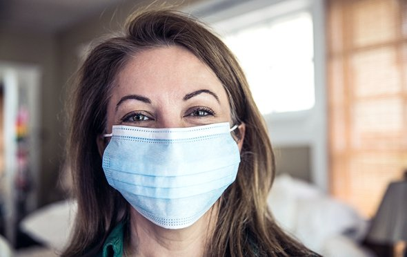 Caregiver with smiling eyes indoors wearing a medical mask.
