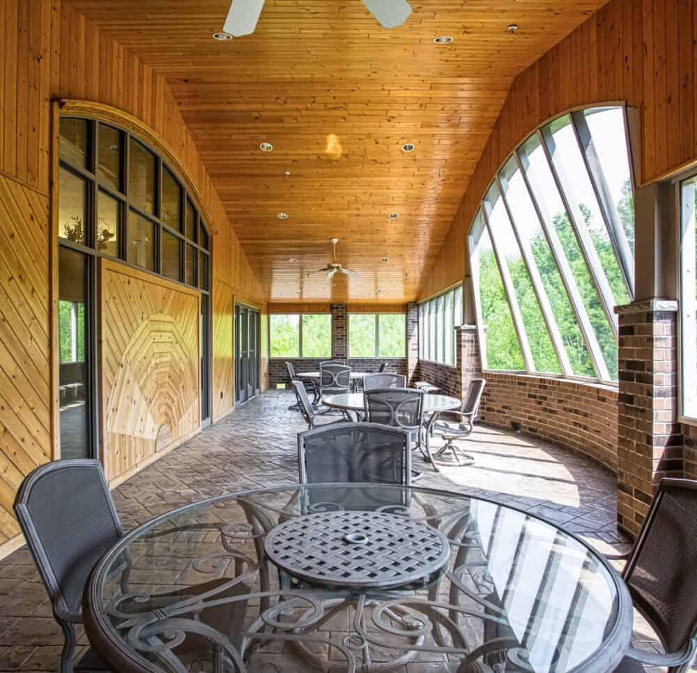 Sun room with seating overlooking the forest at senior living community in Green Bay, Wisconsin.