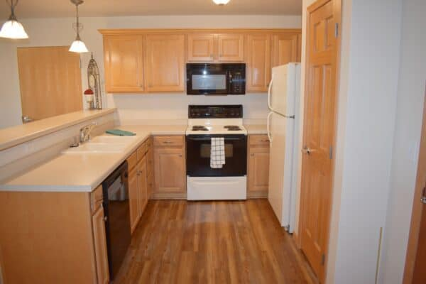 Full kitchen with refrigerator, stove, dishwasher and microwave at a senior living community in Green Bay, Wisconsin.