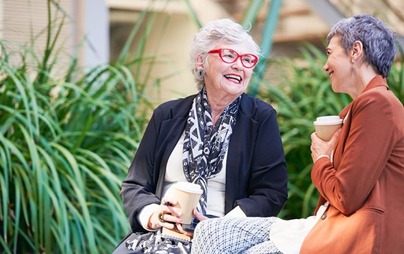 Woman with red glasses holding coffee and talking with a friend outdoors.