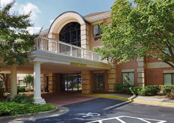 The outside of a senior living community in Raleigh, NC with brick exterior, portico entrance and trees.
