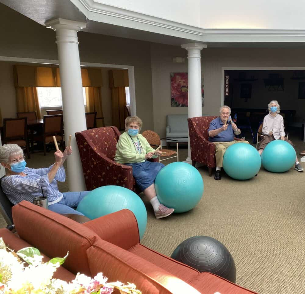 group of seniors in a drumming class at the waterford at mesquite, a senior living community in Mesquite, Texas