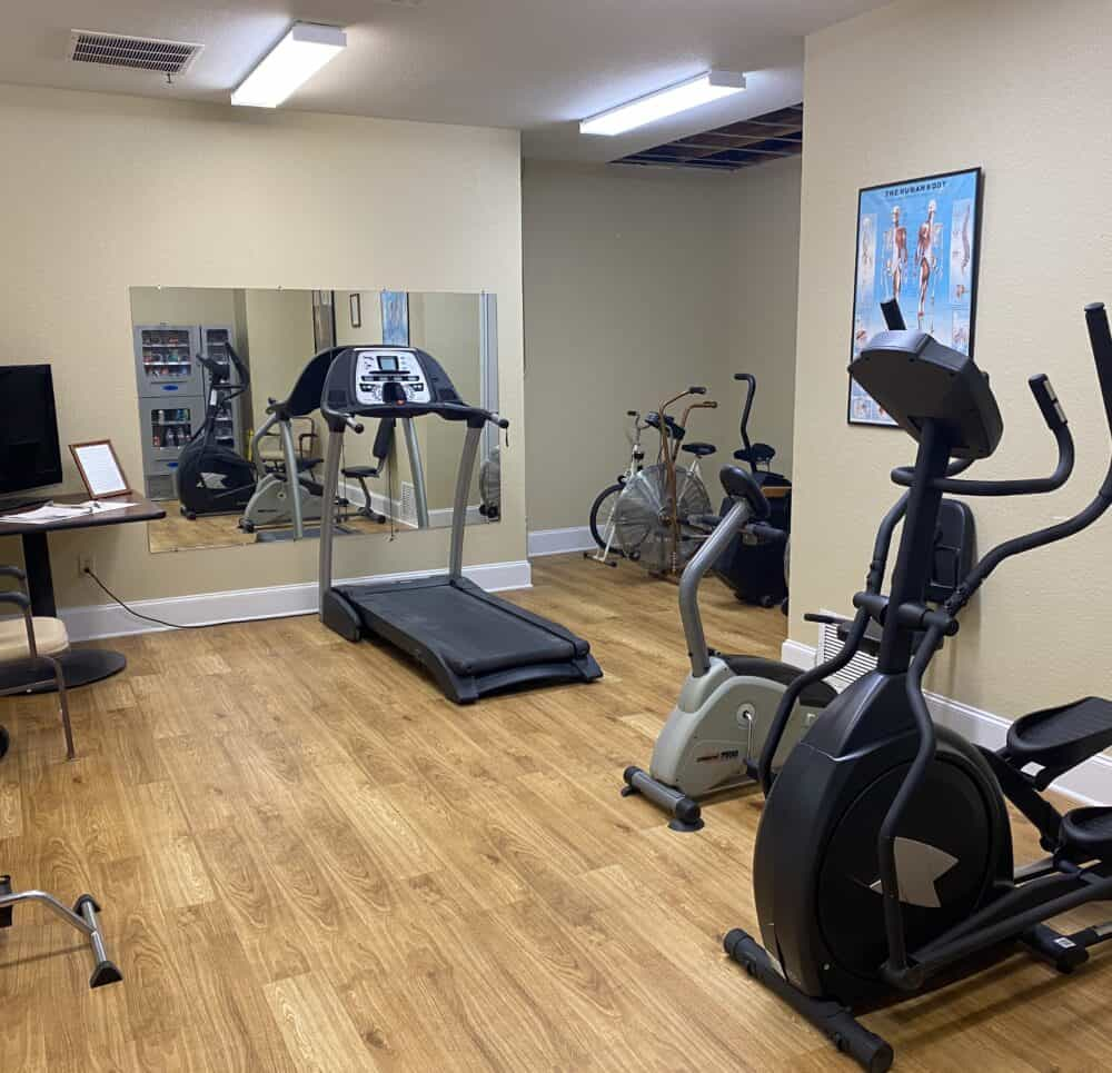 Exercise room at a senior living community in Mesquite, Texas with exercise machines and free weights.