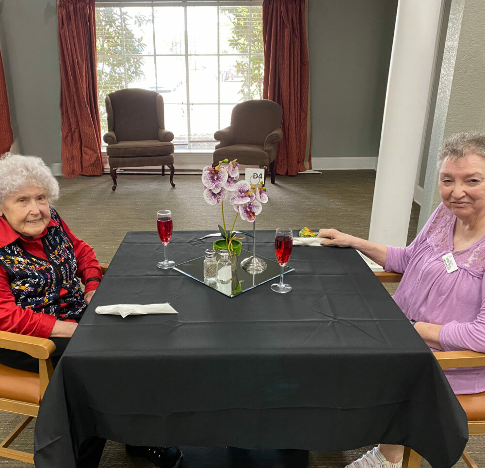 Two senior women smile while at dinner at a senior living community in Mesquite, Texas.