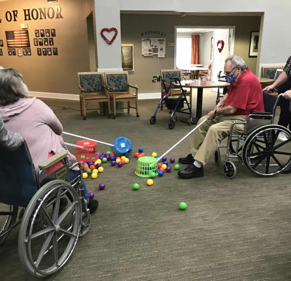 two seniors playing a game at the waterford at mesquite, a senior living community in Mesquite, Texas
