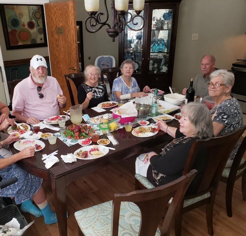 Group of seniors eat a meal together during cooking club at a senior living community in Raleigh, North Carolina.