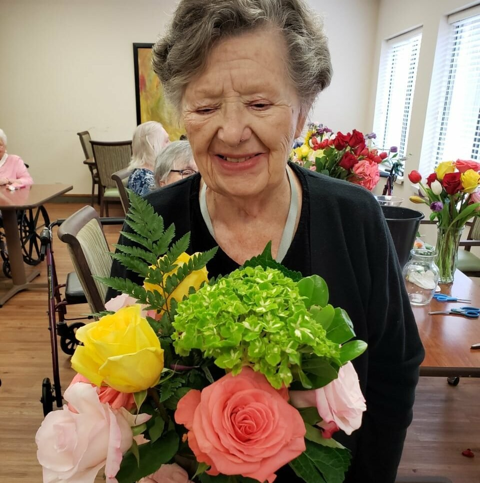 Senior woman smiles while looking down and holding a bouquet of flowers at a senior living community in Raleigh, North Carolina.