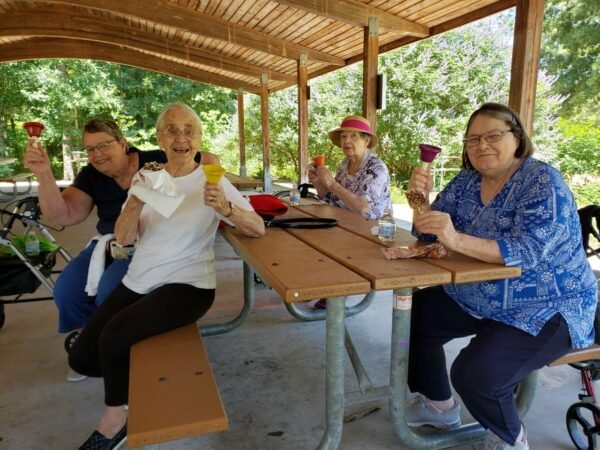 Four senior women smile with their bells while sitting at a park at a senior living community in Raleigh, North Carolina.