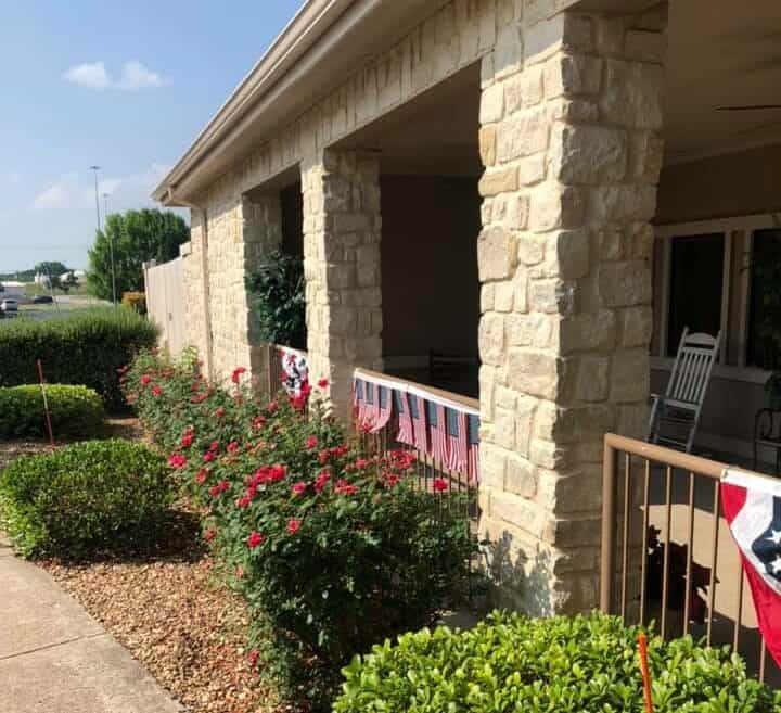 Outdoor view of senior living facility with patriotic decorations in Granbury, Texas.