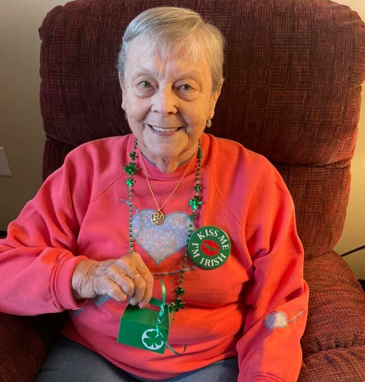 senior woman smiles with Irish decorations at the waterford at west bend, a senior community in wisconsin