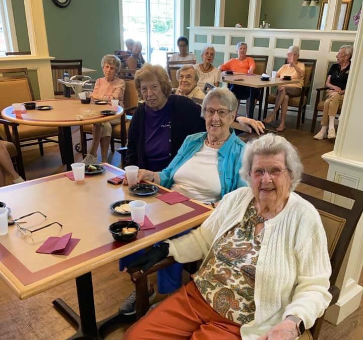three senior women smile while enjoying food and a musical performance