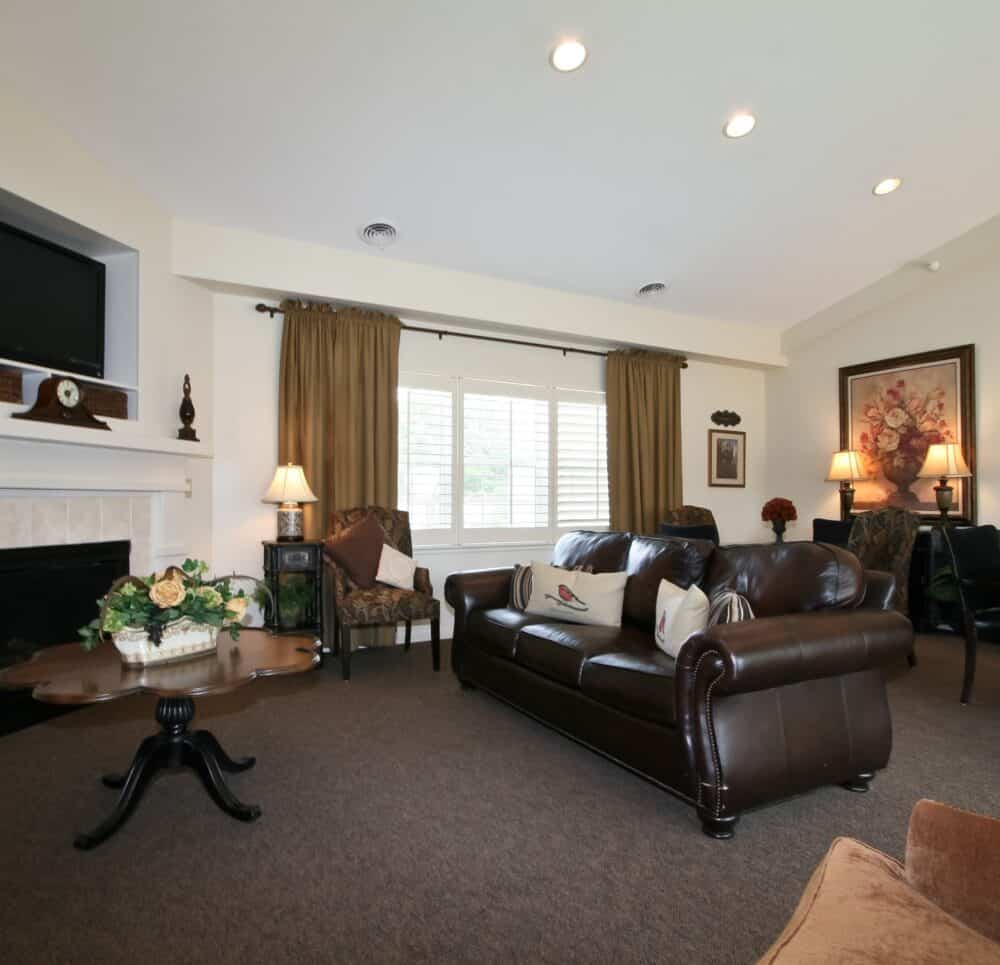 Lounge with couches and a TV at a senior living community in St. Joseph, Missouri.