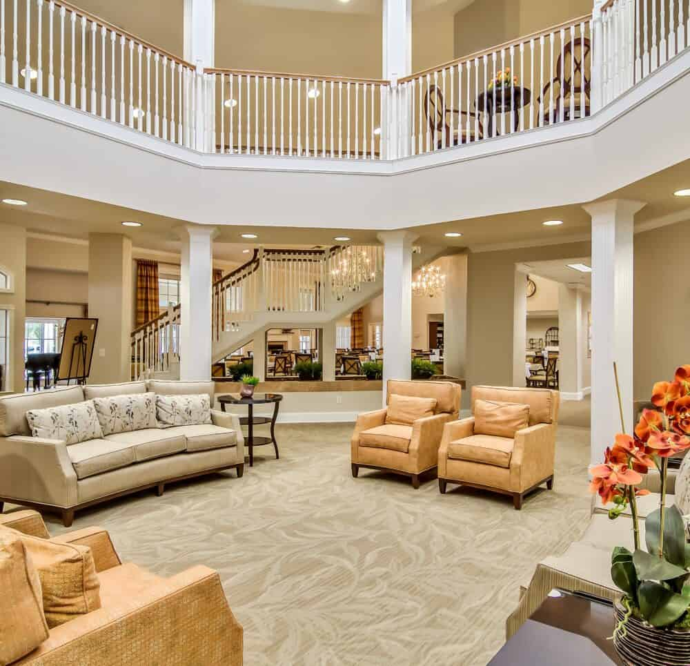 Main lobby and entrance with couches and grand staircase at a senior living community in San Antonio, Texas.