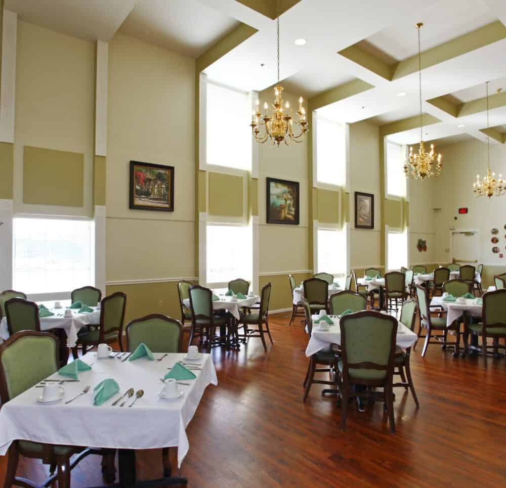 Dining room with vaulted ceiling, comfortable seating and ample natural light at a senior living facility in Omaha, Nebraska