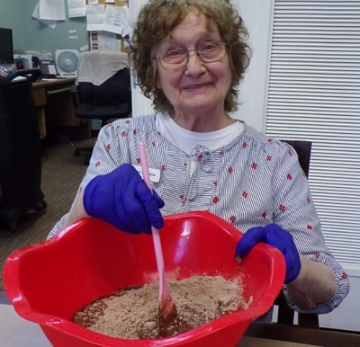 Resident smiling and mixing brownies from scratch in a large bowl.