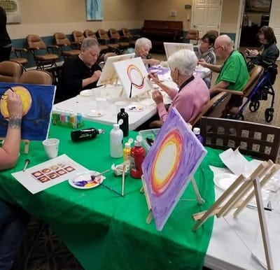 Seniors engaged in a painting class.