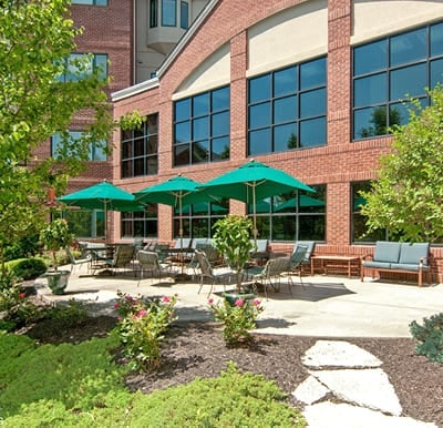 Large patio with umbrella covered tables overlooking a landscaped courtyard.