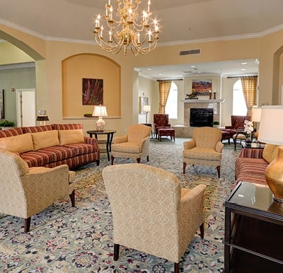 Elegant rotunda with comfortable sofas and armchairs under a beautiful chandelier in Plano, Texas.