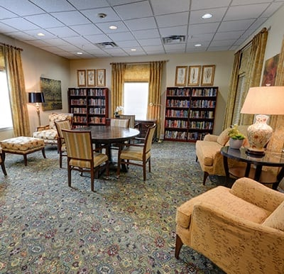 Spacious library with a wall of filled bookshelves, comfortable lounge chairs and a table in Plano, Texas.