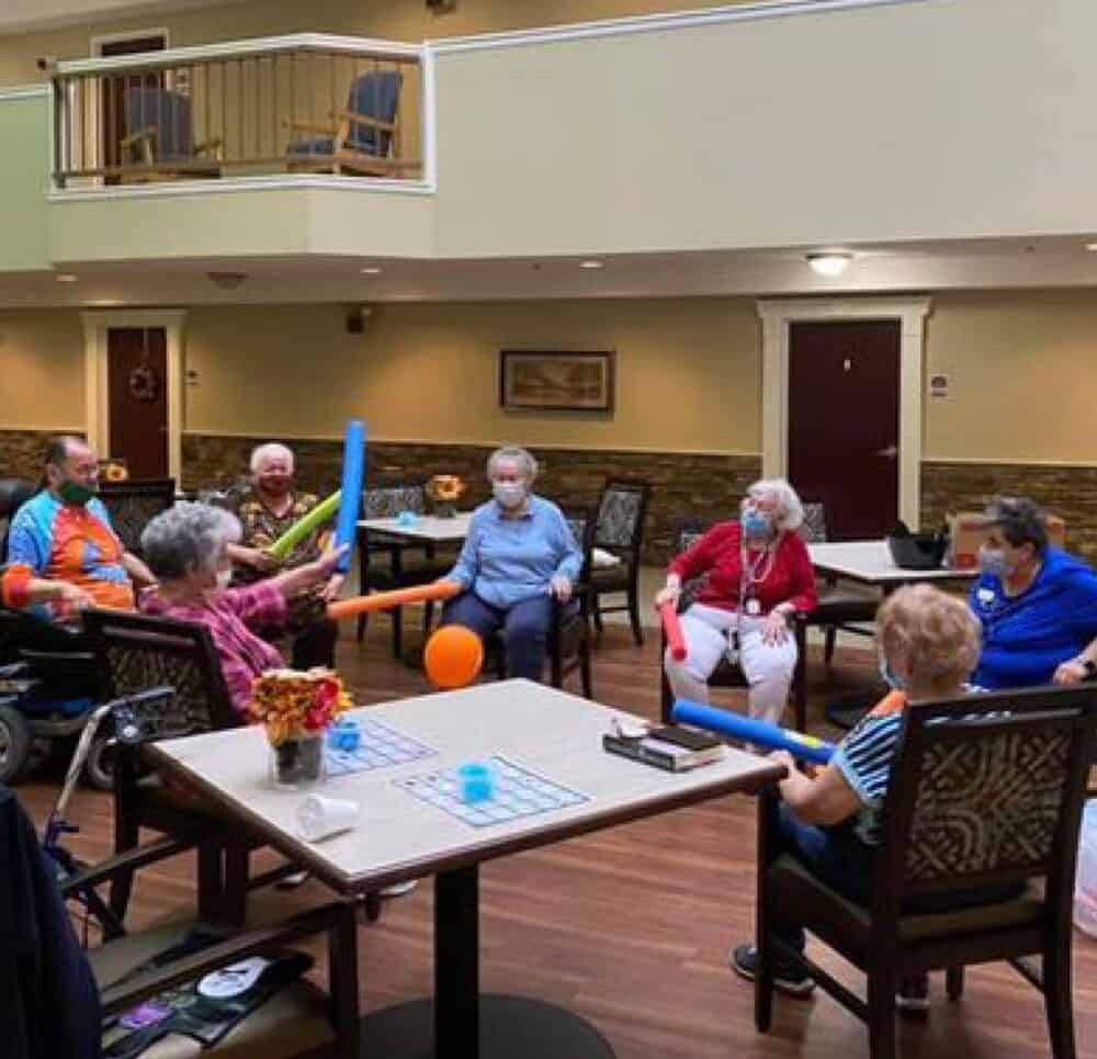 A group of seniors, male and female, enjoying a fun exercise class using pool noodles and a balloon.