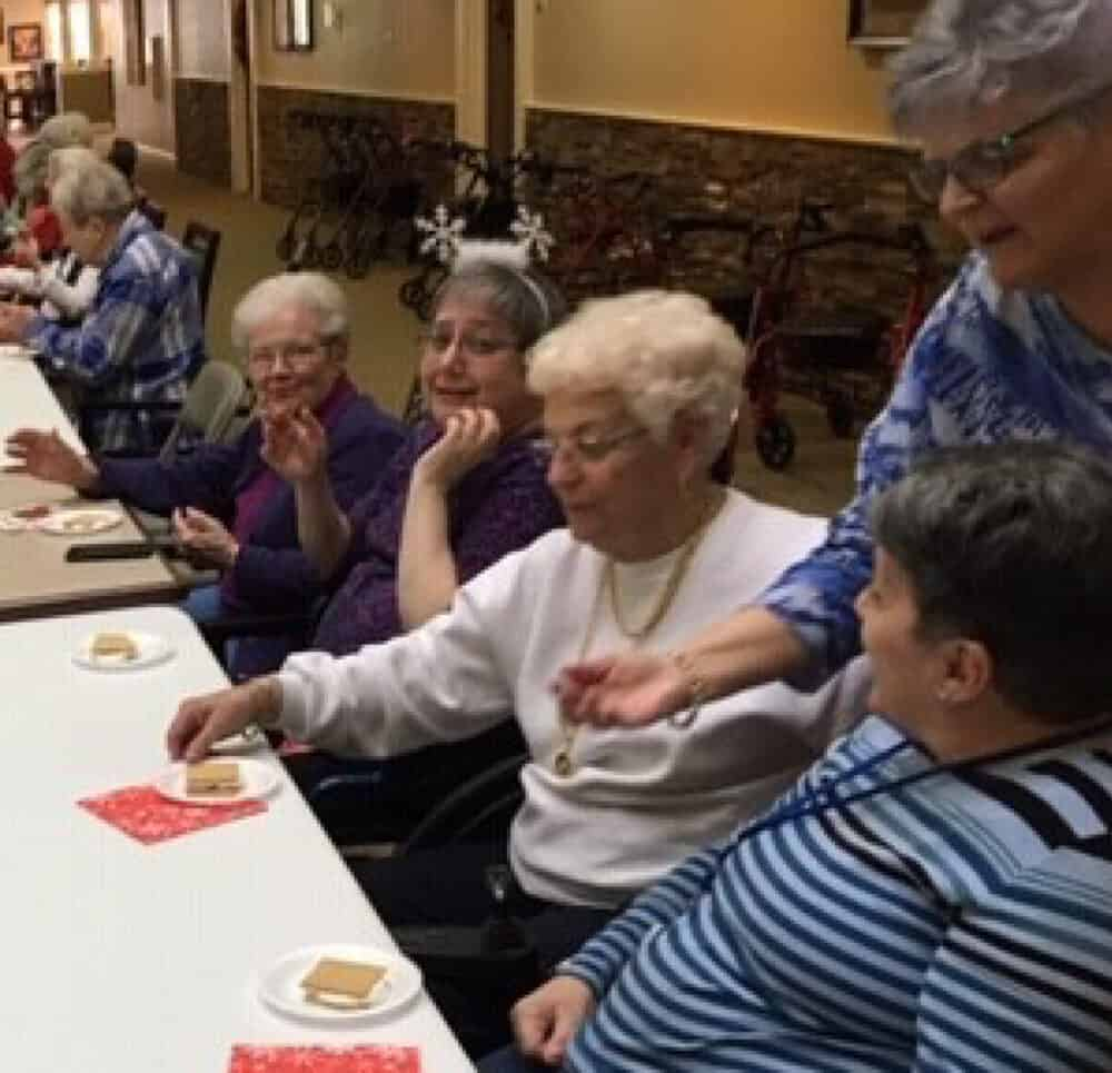 A group of ladies enjoying a s'more during a baking activity.