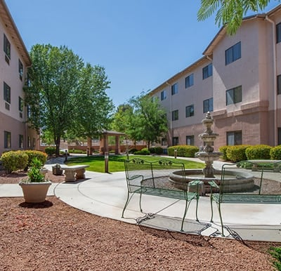 A beautiful courtyard with landscaping, seating and a fountain.