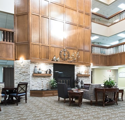 Grand fireplace surrounded by rich wood paneling in a large atrium with comfortable lounge seating.