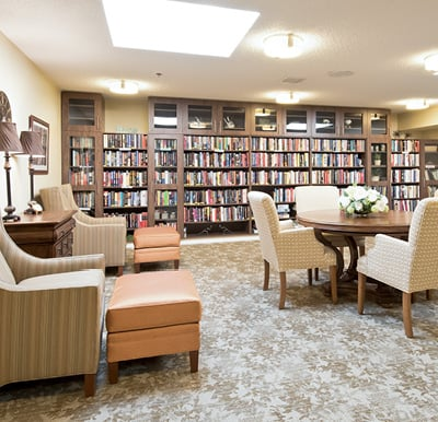 Beautiful library with built-in wood shelving and cabinetry along the back wall, comfortable arm chairs and a table in the center of the room.
