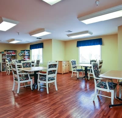 An activity center at a senior living facility with tables and chairs.
