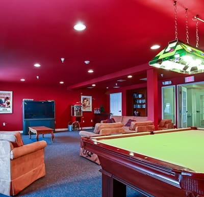Our well-appointed billiards room with comfortable chairs and big-screen TV.