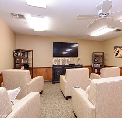 A theatre room with a big-screen TV and lots of comfortable lounge chairs.