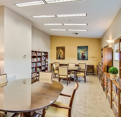 Library with wall-to-wall bookshelves, a lounge seating area and multiple tables with chairs.
