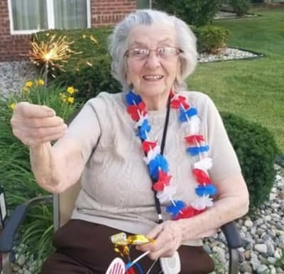 A senior woman holding a sparkler on the Fourth of July.