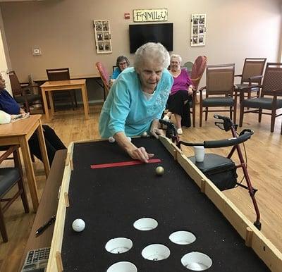 An elderly woman playing shuffleboard at her senior living community.