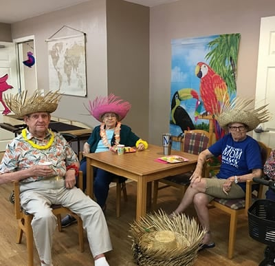 Senior gathered around a table at a themed paradise party in North Richland Hills, Texas.