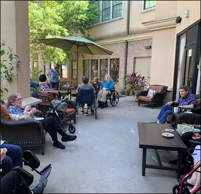 Senior citizens sitting in a courtyard at their assisted living and memory care community in Humble, Texas.